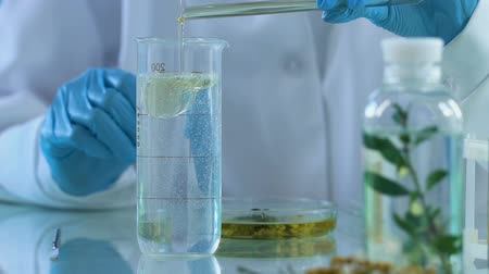 homeopathic : Chemist engaged in mixing extracts of stem cells of plants for anti-aging creams Stock Footage