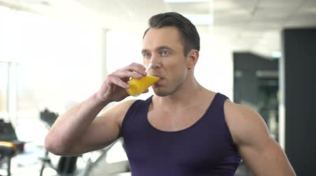 balanced : Bodybuilder drinking fresh orange juice, balanced fitness nutrition, workout