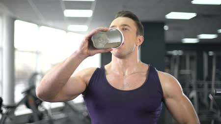 atlet : Muscular man drinking protein shake after workout, healthy diet, bodybuilding