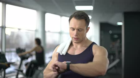 stat : Athlete man checking burned calories in smart watch after workout, innovation