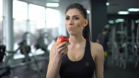 бодибилдинг : Sport female eating apple after workout, balanced nutrition, active lifestyle