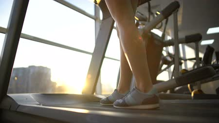 太らせる : Female athlete legs slowly walking treadmill machine, cardio exercise, endurance