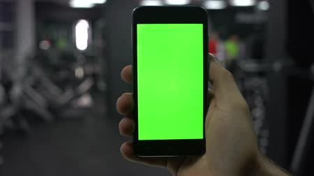 tela : Male hand with smartphone in gym, fitness application results, green screen