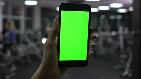 tela : Woman checking amount of burned calories in smartphone application, green screen