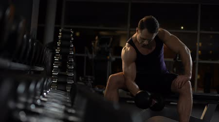 biceps curls : Strong-willed bodybuilder doing seated isolated dumbbell curl, evening workout