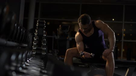 biceps curls : Persistent sportsman doing dumbbell concentration curl, evening workout in gym