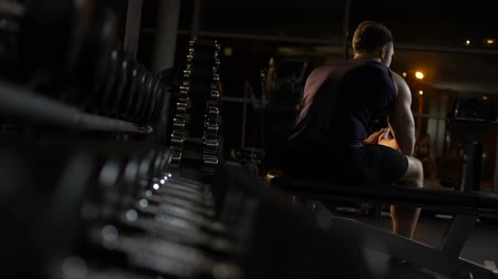 yaşama gücü : Male athlete tired after workout sits on bench, hunches up alone in evening gym
