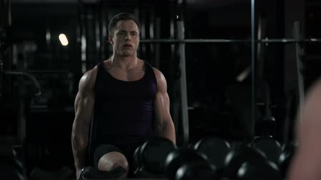 biceps curls : Bodybuilder performs seated side lateral raise, reflection of exercise in mirror