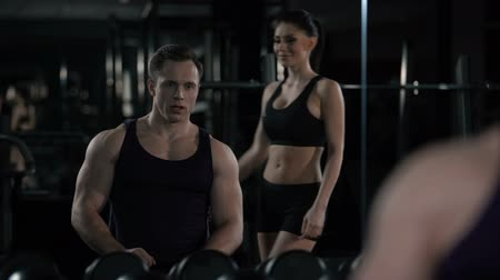 партнеры : Sportive woman and muscular man look in mirror, proud of results after training