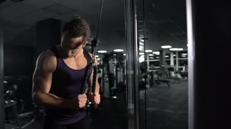 pulling rope : Athletic man training arm muscles, performing triceps cable pushdown exercise