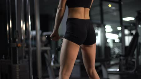 bil : Slim sportive lady training butts in gym, doing cable squat exercise, body care