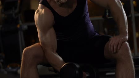 biceps : Handsome bodybuilder lifting heavy dumbbell in gym, active workout and sports.