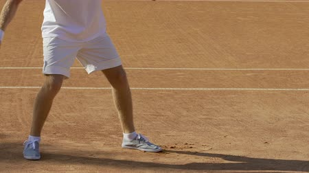 teniszütő : Male amateur tennis player hitting ball with racket, squash competition slow-mo