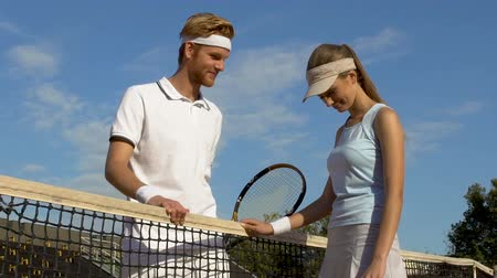 embarrassed : Male tennis player talking to beautiful woman after match at sports complex