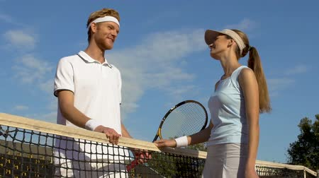 embarrassed : Beautiful sport woman embarrassed talking to man over tennis net.