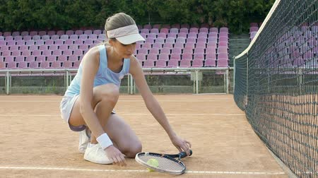 cadarço : Cute female tennis player tying her sport shoes laces before starting match