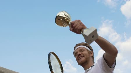 честь : Handsome man showing trophy and racket over head, celebrating tournament victory
