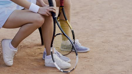 pontão : Feet of male and female tennis players sitting at court, waiting for results Stock Footage