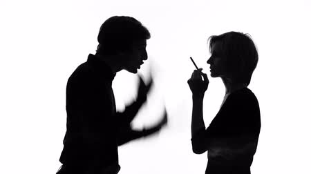 gritante : Angry man shouting at his girlfriend smoking cigarette in front of him, quarrel