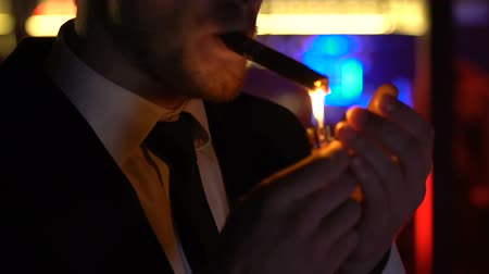 seçkinler : Confident man in suit lighting cigar, relaxing at night party, elite mens club Stok Video