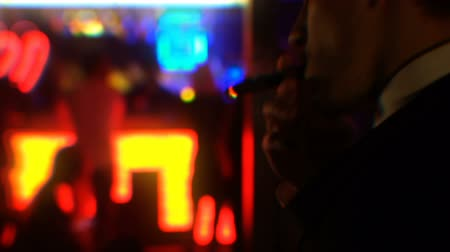 cigar : Young businessman smoking cigar and looking at dancing girls in strip club