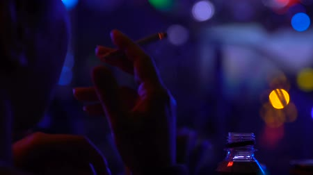tabaco : Smoking clubber relaxing cigarette in night club, party atmosphere, chill out