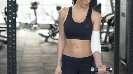штамм : Sportswoman suffering from elbow pain raising dumbbell bandaged hand. Стоковые видеозаписи