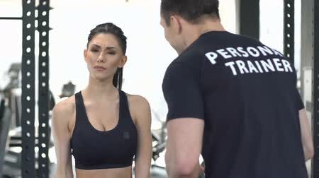sustain : Personal trainer encourages woman to exercise with dumbbell, healthy lifestyle