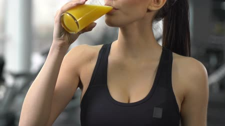 sede : Slim lady drinking juice after workout in gym, balance of diet and exercises Vídeos