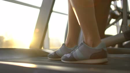 太らせる : Woman walking slowly on treadmill, evening workout in gym on window background