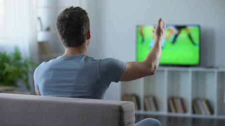 поражение : Man watching football match on big screen at home cheering his favorite team