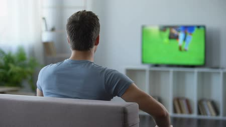 поражение : Young man watching soccer match home, criticizing football team for defeat