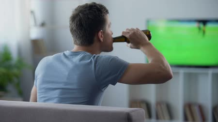 entusiasmo : Bachelor watching football match supporting national team, drinking beer on sofa
