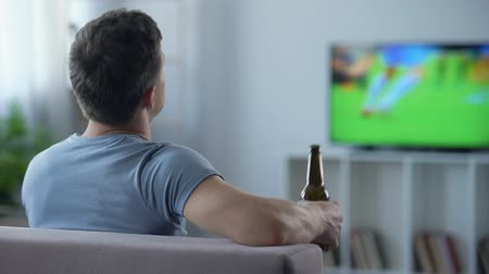 favori : Male supporter watching football drinking beer, disappointed with tie in match