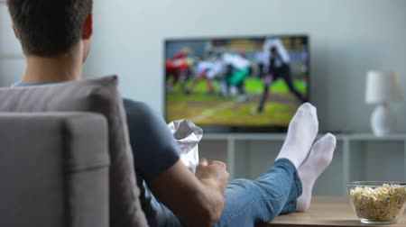 lelkesedés : Man watching american football eating snacks on couch home, weekend leisure