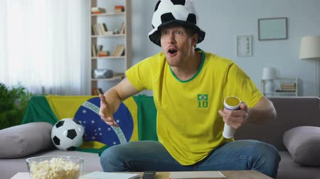 favori : Football fan actively supports Brazil team at championship, watching match home Stok Video