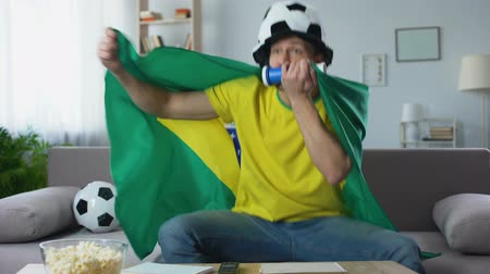 world cup : Happy fan cheering Brazil team celebrating successful match, watching game on tv Stock Footage