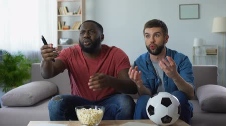kural : Multiethnic guys watching football match, frustrated by defeat of favourite team Stok Video