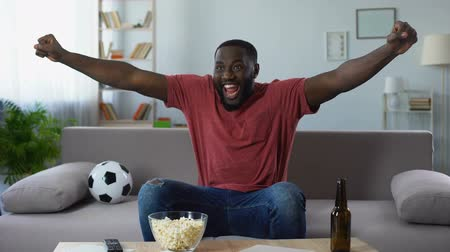 world cup : Afro-american man watching sports competition, happy fan victoriously screaming