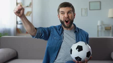 rejoice : Cheerful guy loudly screaming watching football match, successful game result