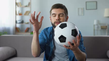 league : Young man nervously watching football match on tv home, frustrated at team loss