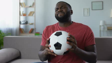 負け : Excited football fan watching game home, unhappy with team failure in match