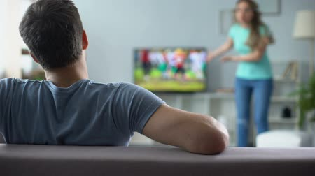 přestupek : Woman quarreling, man watching football match, ignoring conflict, relationship