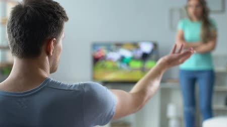 přestupek : Girl nervously screaming at guy, forbidding him to watch tv sports competition
