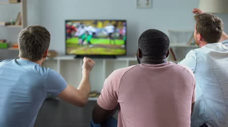 actively : Male friends gather to watch football competition on big screen, sofa experts