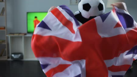 atributo : Man holding Great Britain flag, supporter watching football game on tv at home