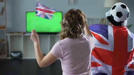 támogató : British fans watching football match on tv at home, supporting national team