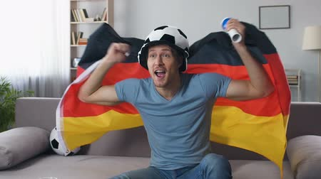 roaring : German football fan celebrating victory of national team, jumping with flag Stock Footage