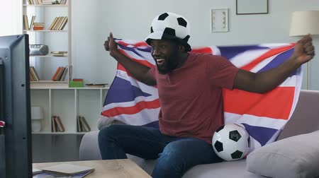 roaring : British football fan excited by game, cheering for team with national flag