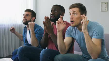 nadšení : Men praying sincerely for team winning, roaring happily because of victory